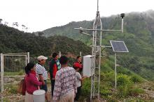 A group of people gathers near a weather monitoring station.