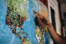 Close-up of a world map with numerous colored pins and a hand pointing to an area on it.