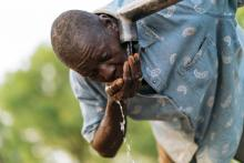 A man drinks from a water tap.