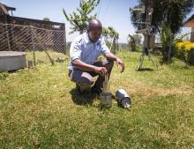 Worker examining a rain gauge at a meteorological station in Kenya.