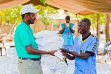 Men receiving his mosquito net LLIN during mass campaign in Casamance, Senegal.jpg