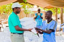 Men receiving his mosquito net LLIN during mass campaign in Casamance, Senegal.jpg