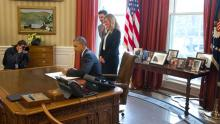President Obama signs an executive order in the Oval Office to set new targets for reductions in greenhouse gas emissions by the federal government.