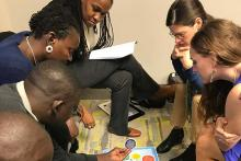 A group of people sit and look at a game board on the floor.
