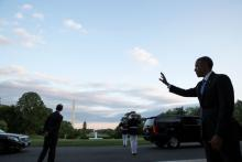 President Obama waves to guests from White House.