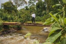 SWP Team Leader Gordon Mumbo stands on a small bridge over a river.
