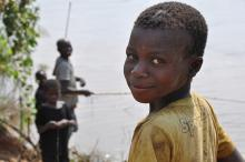 Mozambican boy fishing with friends near lake looks back at camera.