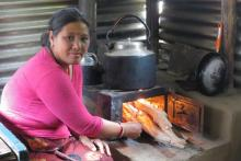 A woman puts wood into a cookstove.