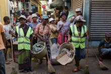 An all-woman work crew walks down a narrow street.