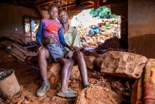 Man and boy sit together on rubble