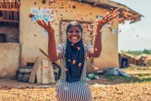A woman smiles at the camera as she throws dried cocoa nibs into the air.