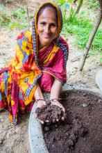 A woman in a colorful dress kneels and cups a handful of dark brown compost while smiling for the camera.