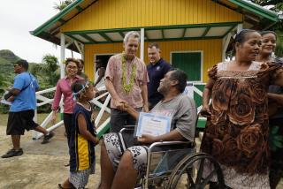 A man in a wheelchair accepts a certificate of ownership outside of his new house.