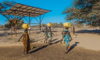 Women with water barrels on their heads walk away from the camera.